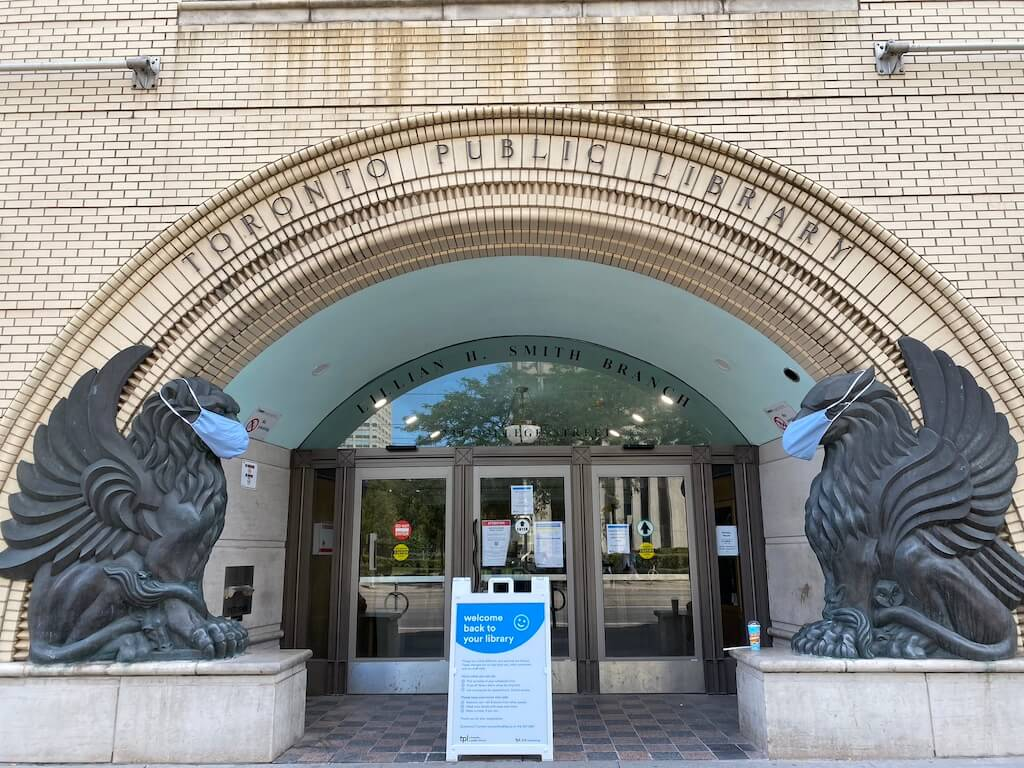 Toronto Public Library, griffin sculptures at the door wearing masks